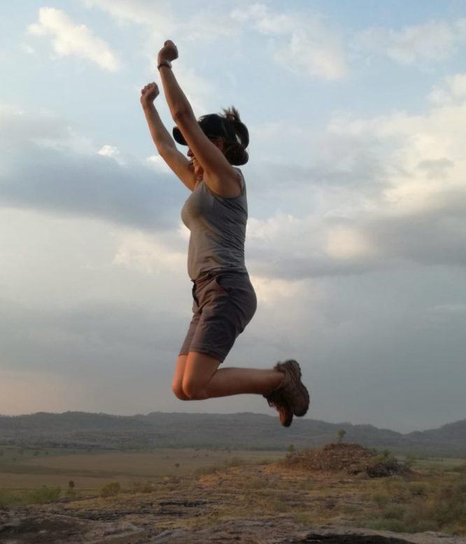 eine Frau macht einen Luftsprung auf einem Felsplateau mit Fernblick auf eine weite Landschaft mit Bergkette im Hintergrund